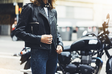 Girl unfastens black leather jacket on background motorcycle in sun flare atmospheric city, hipster biker closeup, motorbike street lifestyle, traveler planing bike route in summer holiday concept