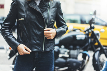 Girl unfastens black leather jacket on background motorcycle in sun flare city, hipster biker female hands closeup, motorbike street lifestyle, traveler planing bike route in summer holiday concept