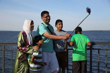 A Muslim family  uses a selfie stick to take photos after Eid al-Adha prayers in Bensonhurst Park in Brooklyn, New York