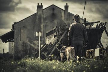 Une femme se promène avec son chien dans paysage apocalyptique de bateau et batiment abandonné