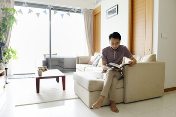 Man relaxing at home reading a book