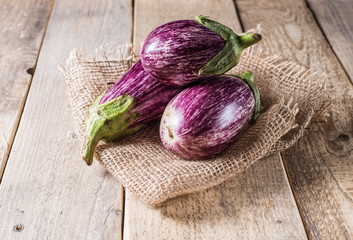 Harvest of striped eggplant on a wooden background