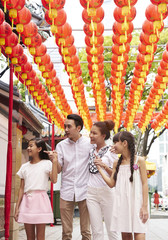 Family of four strolling down Telok Ayer during Chinese New Year
