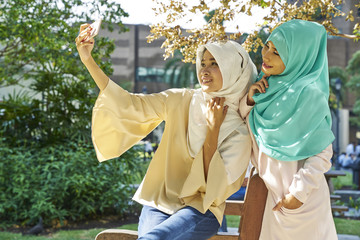 Two women in a tudung taking selfies at the park in Singapore