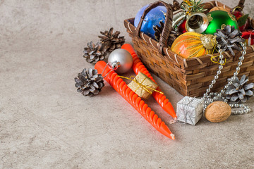 Preparing for Christmas. Wicker brown basket with Christmas toys, cones, red twisted candles and small shiny boxes with gifts on a gray background.