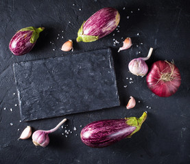 Some eggplants, garlic and red onion on a black board and background. Copy past. Top view.