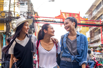 Three pretty asian girls are walking around and having fun in Chinatown, Bangkok