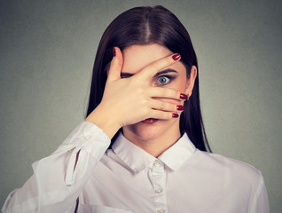 Scared young woman peeking through her fingers