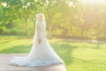 Portrait of a beautiful muslim bride with make up in white wedding dress with beautiful white headdress natural light.