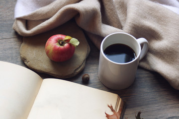Fall still life with apples, open book and leaves over rustic wooden background, horizontal
