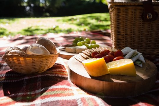 Bun, cheese, cracker biscuit on picnic blanket