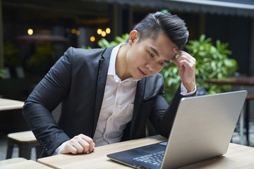 Young businessman busy with work on his laptop