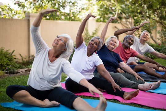Senior people with arms raised exercising at park