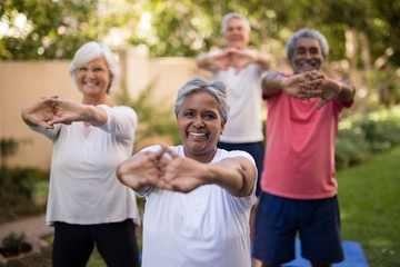 Portrait of senior woman stretching arms with friends