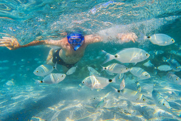 Young man snorkeling in underwater coral reef on tropical island.
