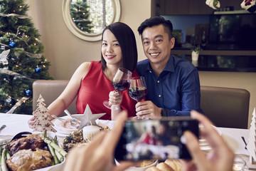 Joyful couple taking a photo on Christmas day