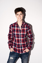 Smiling brunette with short hair in checked shirts and jeans