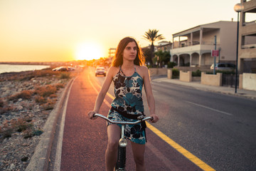 Young woman with a bike during a sunset