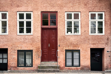 Residential house with red wooden door and windows