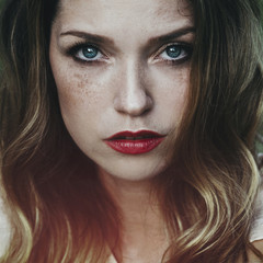 Artistic portrait of a beautiful young woman with freckles and blue eyes