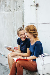 Portrait of a two female colleague with tablet and notebook outside