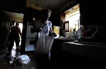 Nancy McBride collects items from her flooded kitchen as she returned to her home for the first time since Harvey floodwaters arrived in Houston