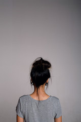 Back view of brunette girl with hairstyle against of grey background