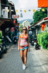 Sexy tanned blonde woman have fun on vacation walking on the street in colorful dress