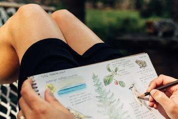 Woman's hands sketching in her journal