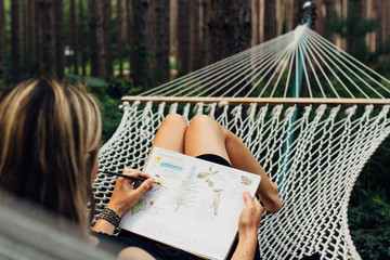 Woman lounging on a hammock drawing in her journal