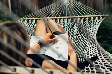Woman laying on a hammock drawing in her nature journal