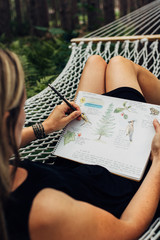 Female drawing in her nature journal on a hammock