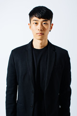 Portrait of an attractive asian man wearing a black suit over white background.