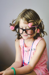 Portrait of silly girl with hair in curlers and oversize glasses