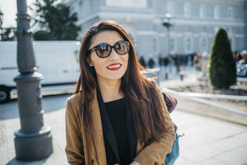 Cheerful Chinese tourist woman walking around plaza ramales of Madrid