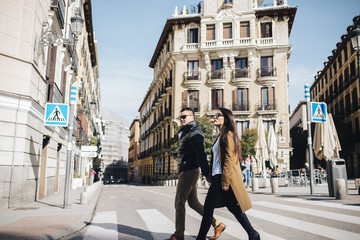 Asian Chinese couple strolling down Plaza Ramales in Madrid