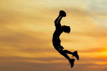 Boy leaps for the ball.