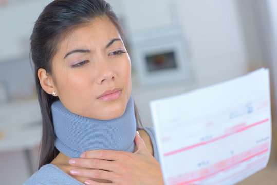 young woman wearing neck brace reading insurance letter