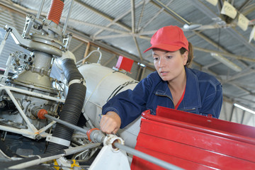 female mechanic working on helicopter engine