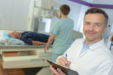 happy male doctor with clipboard writing prescription