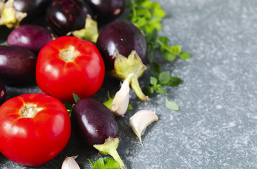 Tomatoes, eggplants and garlic on stone texture background.