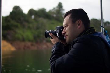 Hombre latino tomando fotos con cámara profesional