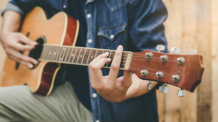 Cropped shot of man's hands playing acoustic guitar, vintage tone