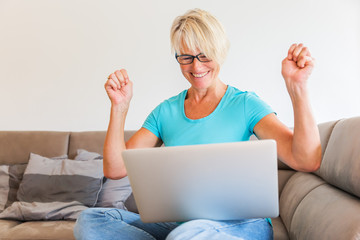 mature woman sits rejoicing in front of a laptop