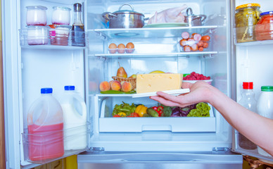 Open refrigerator filled with food. Man holding cheese