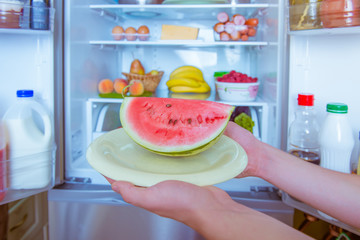 Open refrigerator filled with food. Hands holding watermelon