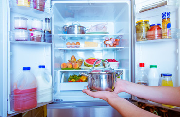 Open refrigerator filled with food. man holding a pot