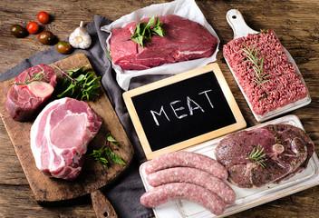 Keuken foto achterwand Vlees Different types of fresh raw meat on a dark wooden background.