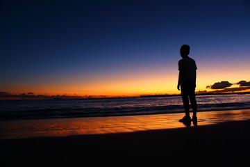 夕暮れの海辺に立つ子供のシルエット ハワイ