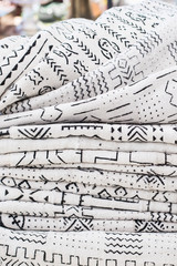 African textiles at a market stall featuring black and white patterns on hand-woven cloth by a woman from Ghana